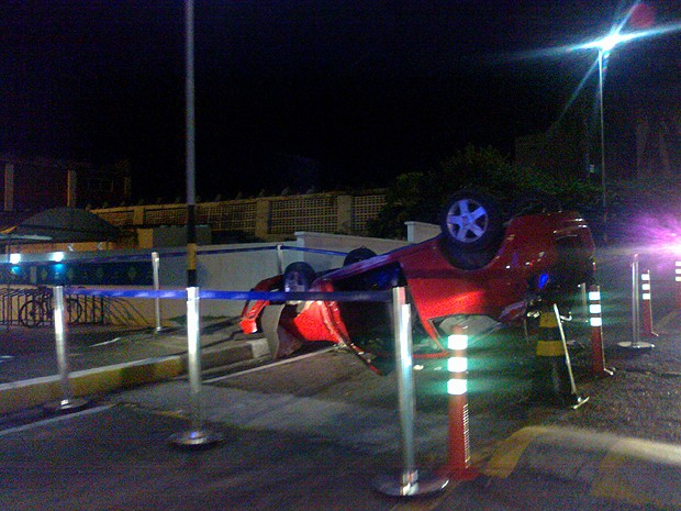 Mulher capota carro na entrada do estacionamento.