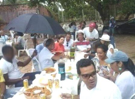 Camaçari: Funcionário segura guarda-chuva para prefeito durante almoço